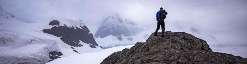 Travellers hikes up rock in Antarctica in snow