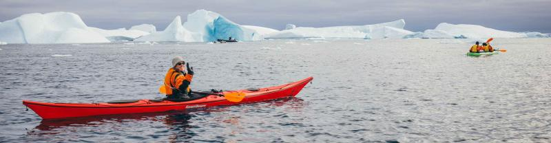 Travellers kayak among the icebergs in Antarctica