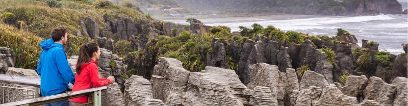 Couple admiring Punakaiki Pancake Rocks from viewpoint, South Island, New Zealand