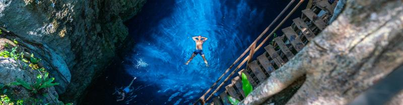 Traveller floating in blue waters in cenote, Mexico