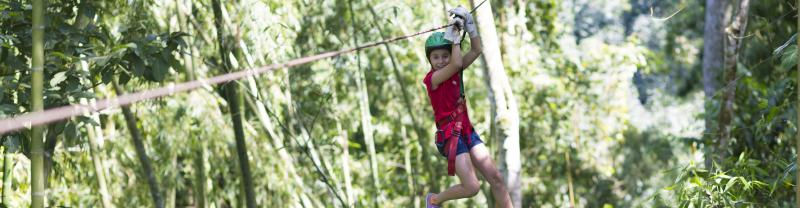 girl ziplining through trees