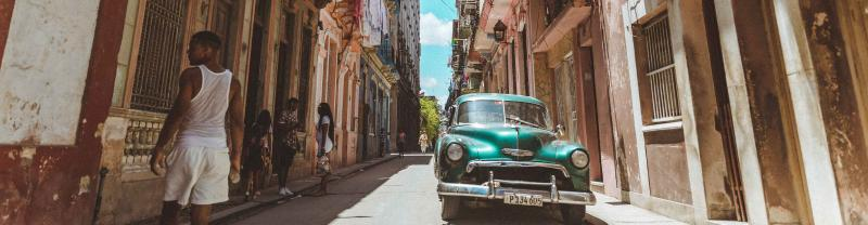 Cars parked down small side street of Havana