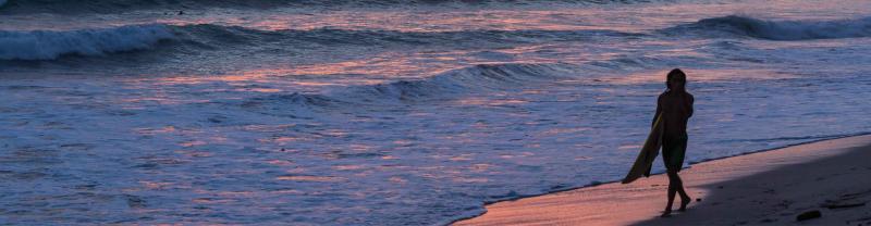 Surfer walks along Costa Rican beach and sunset