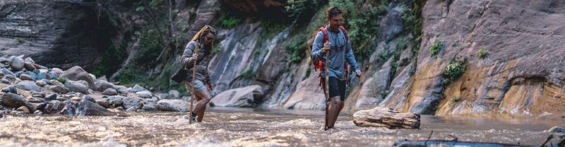 Two hikers trekking through water between the narrows of Zion
