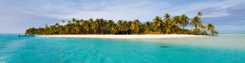 Tropical Island off Aitutaki in the Cook Islands with palm trees and crystal clear water