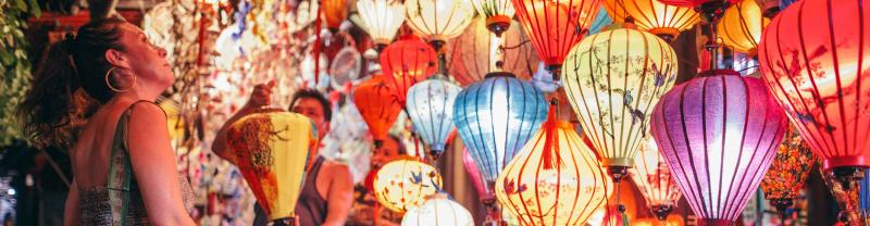 Traveller looks at lanterns at local market in Hoi An, Vietnam