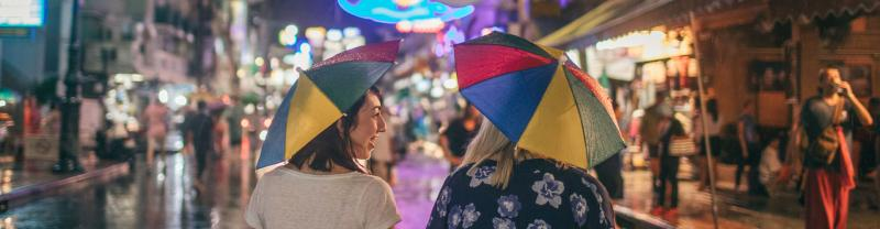 Two travellers wander down busy Bangkok street at night with umbrellas