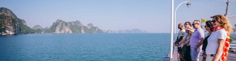 Passengers on board boat look out at the mountainous islands of Halong bay
