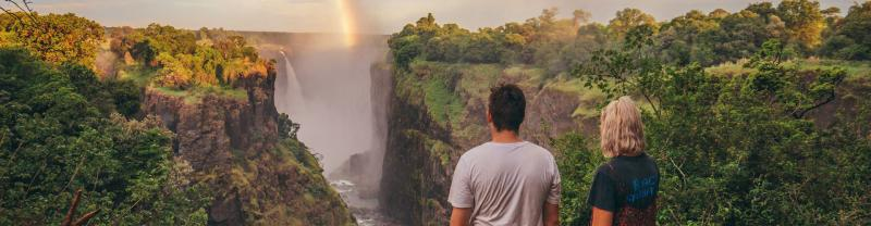 Two travellers look at Victoria falls as rainbow forms in distance