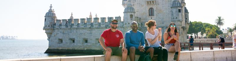 Intrepid Travel group sitting on river bank in front of Belem Tower, Lisbon, Portugal