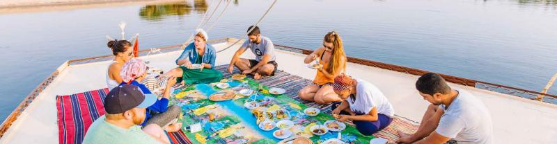 Travellers enjoy lunch aboard a felucca cruise, Aswan