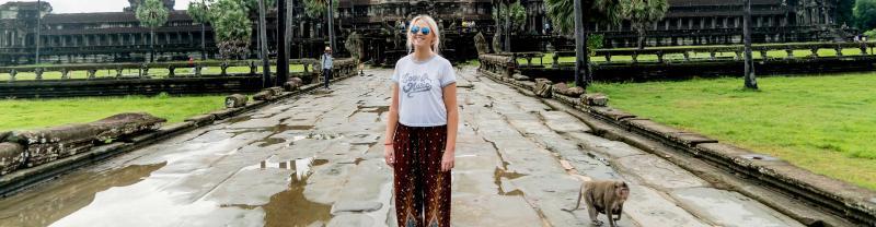 Young traveller smiling at angkor wat, cambodia