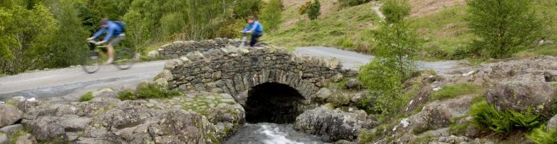 Cyclists crossing a small stone bridge in the Lake District, United Kingdom