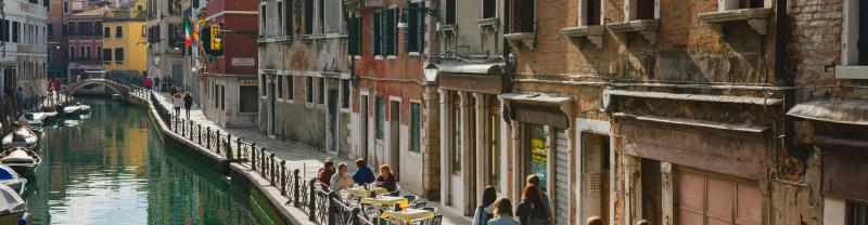 View of travellers walking along a canal in Venice