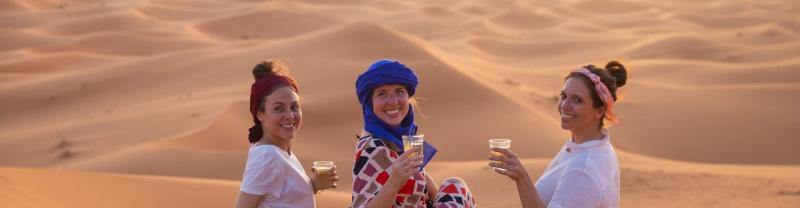 Travelles drinking tea on sand dunes, Sahara Desert, Morocco