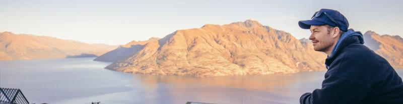 Man looks out over the Queenstown skyline with Lake Wakatipu in the distance.