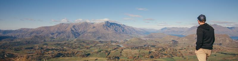 Man looking out over a mountain range in Queenstown, New Zealand