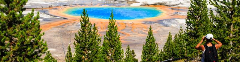 A hiker standing at the bird's eye lookout for Grand Prismatic Spring