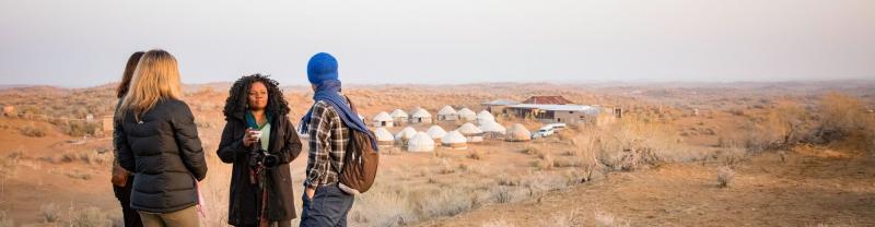 Travellers standing outside desert yurt camp, Uzbekistan