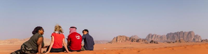 Travellers sitting on sand dune, Wadi Rum Jordan