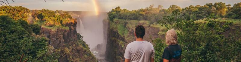 Travellers looking at rainbow over Victoria Falls