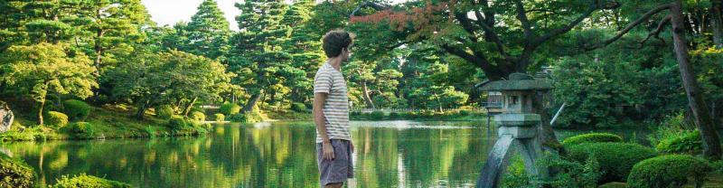 Traveller walks across bridge in Kenrokuen Garden