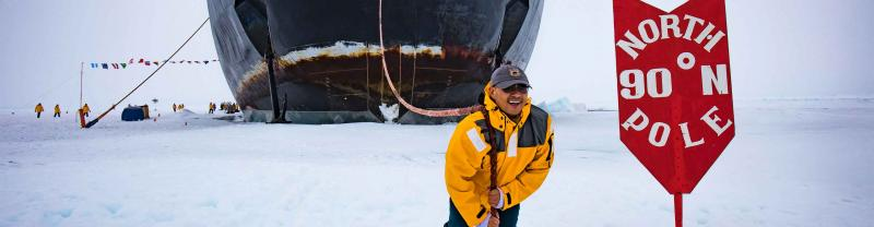 Traveller poses with north pole sign and boat