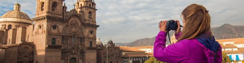 A traveler taking a photo in Cusco, Peru