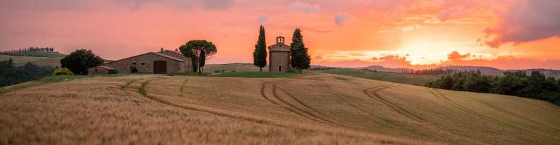 Pink and orange sun set over the rolling Tuscan hills