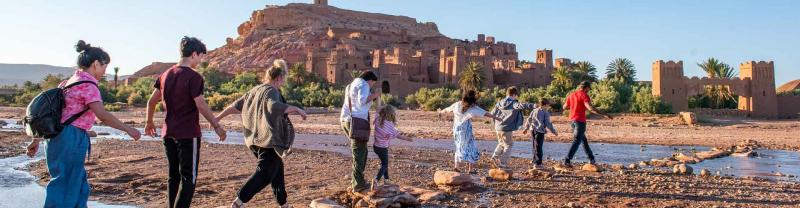 Group of travellers walk across stepping stones in Ait Benhaddou