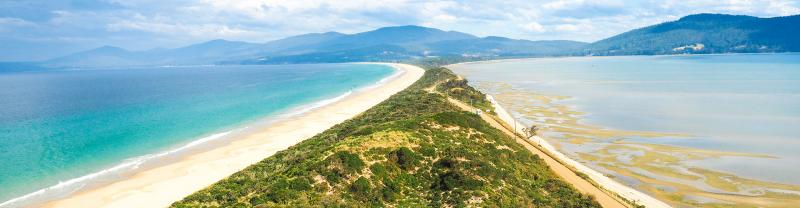 Long strip of white sand and blue water in Bruny Island, Tasmania