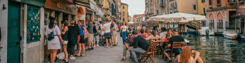 Italian locals and tourists gather on the street outside restaurant in Venice