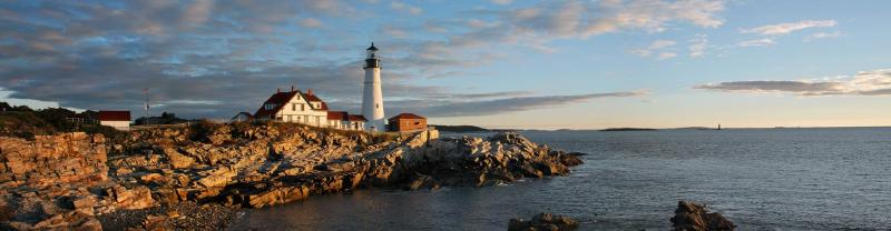 A Portland lighthouse on the coast of Maine at sunset.