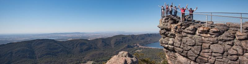 Visitors stand on the edge of a cliff at the Grampians in Victoria