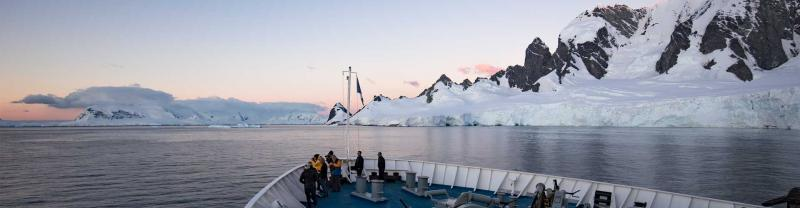 Travellers stand on bow of ship looking at Antarctic coastline