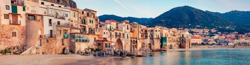 Sunset on the Mediterranean sea with mountains and quaint houses of Sicily