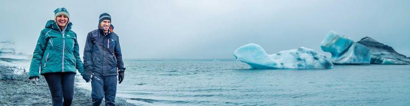 Travellers walk along the coastline at Jokulsaron glacier, Iceland