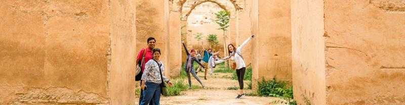 Group of travellers posing in archway, Meknes, Morocco