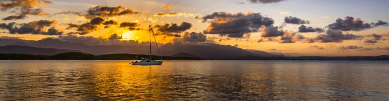 A boat sailing on the water with the sunset behind them in Port Douglas.