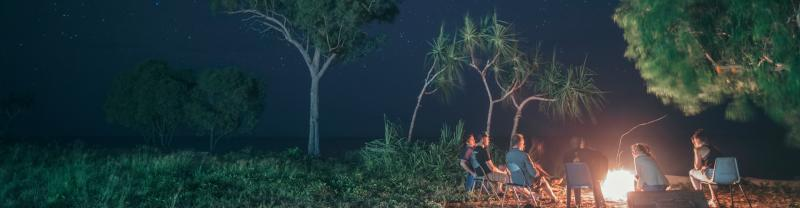 Group of travellers sitting around the campfire