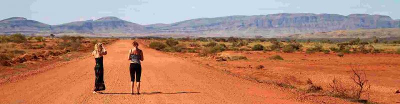 Travellers standing on a desert road in Western Australia