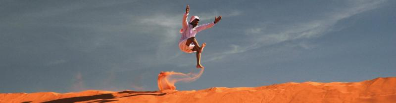 Local man running and jumping on orange sand dune against blue sky