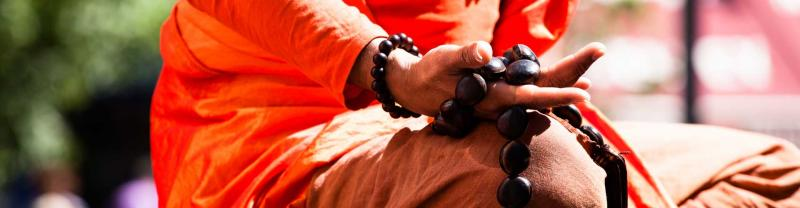 Cambodian monk holds buddhist beads