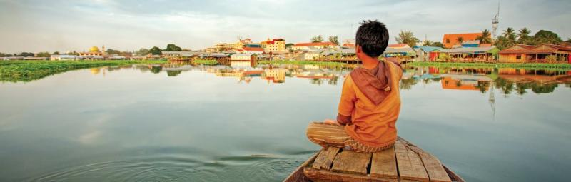 Monk dressed in orange looking out onto a river in Cambodia