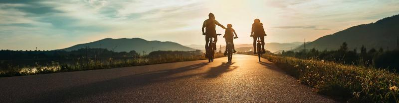 Group of travellers cycling at sunset