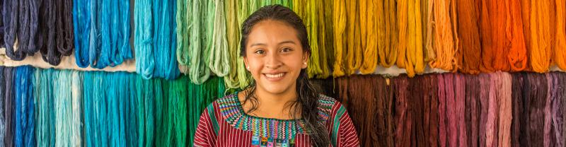 Young woman in traditional clothing standing in front of colourful yarns of wool hanging on the wall