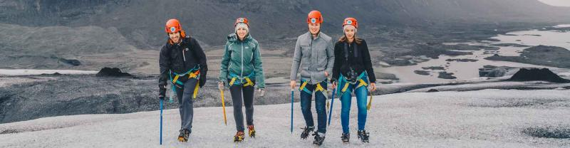 Travellers in safety gear as they hike glacier in Iceland