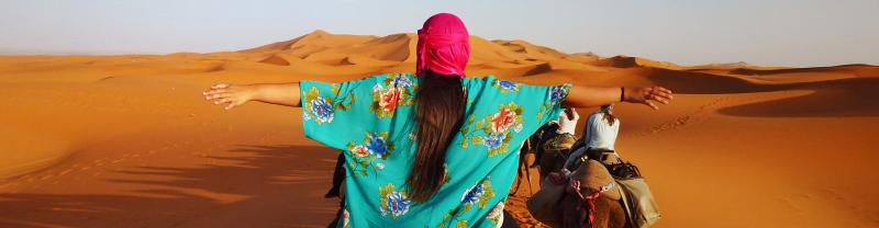 Traveller riding camel in Sahara desert with arms raised looking at sand dunes
