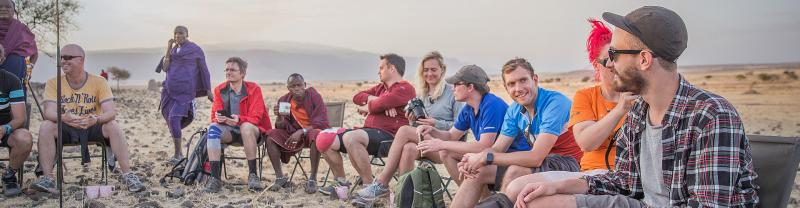 Group of travellers at a seated gathering amongst masai warriors on the Serengeti in Tanzania