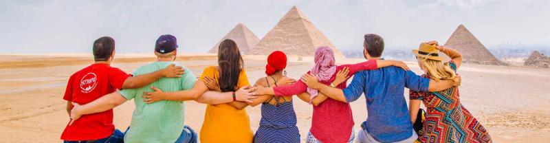 Group of travellers marvel at the pyramids in Cairo
